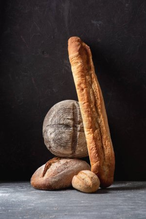 close up view of loafs of ciabatta and baguette on black background