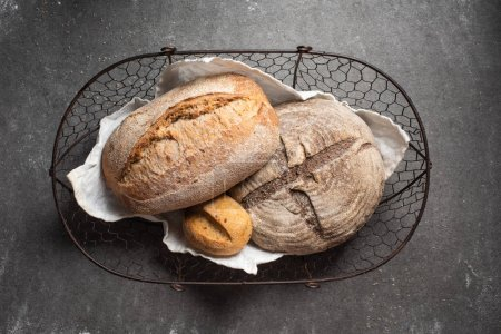 Photo for Top view of ciabatta bread in basket on grey backdrop - Royalty Free Image