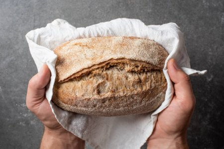 cropped shot of man holding loaf of bread in hands on grey backdrop