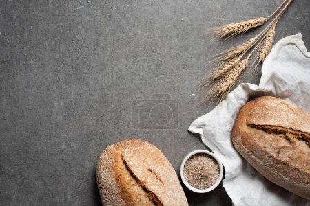 Photo for Flat lay with arranged bread and wheat on grey tabletop - Royalty Free Image