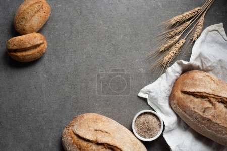 Photo for Flat lay with arranged bread loafs and wheat on grey tabletop - Royalty Free Image