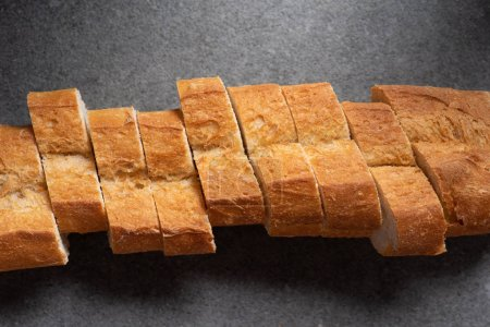 top view of cut baguette on grey surface