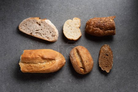 Photo for Flat lay with pieces of various bread on grey tabletop - Royalty Free Image