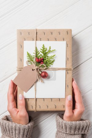 cropped image of woman with decorated christmas gift box at wooden table