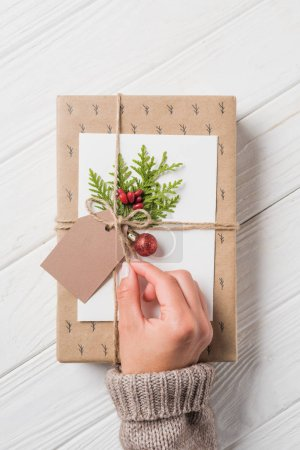 partial view of woman decorating christmas gift box at wooden table