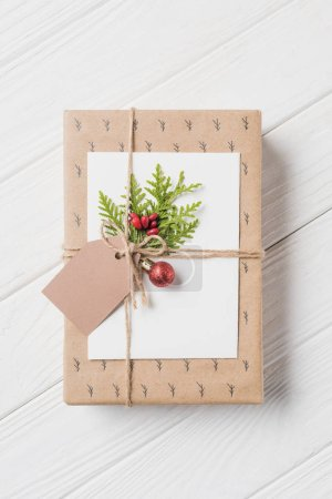 elevated view of decorated gift box with evergreen branch and christmas baubles on wooden table