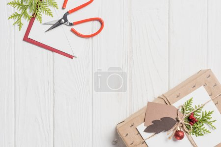 elevated view of decorated christmas present with baubles on wooden table