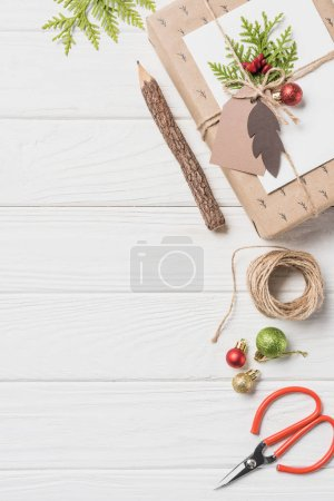 Photo for Top view of decorated christmas present with baubles near wooden pencil and scissors on wooden table - Royalty Free Image
