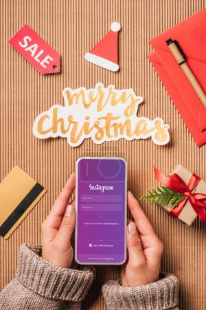 partial view of woman holding smartphone with instagram on screen over surface with sale sign, credit card and merry christmas lettering