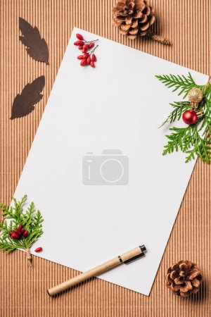 top view of empty paper and evergreen branches with christmas baubles on surface
