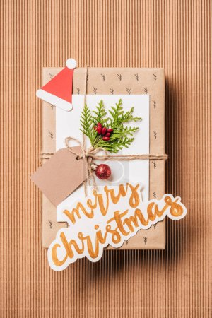flat lay with gift box with baubles, evergreen branch and merry christmas lettering on surface