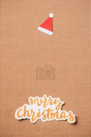 top view of santa hat and merry christmas lettering on surface