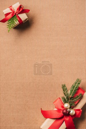 elevated view of decorated gift boxes with christmas baubles on surface
