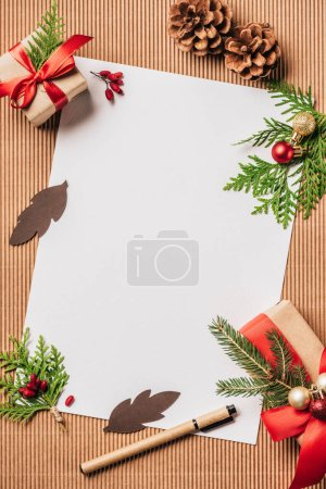 elevated view of empty paper, evergreen cones, decorated gift boxes with christmas baubles on surface