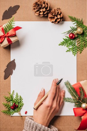 cropped image of woman with pen at surface with empty paper and decorated christmas gift boxes with baubles and evergreen branches