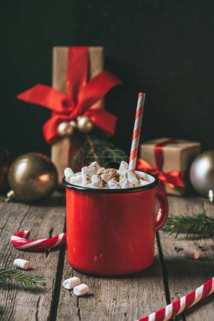 cup of hot cocoa with marshmallows on wooden table with christmas presents