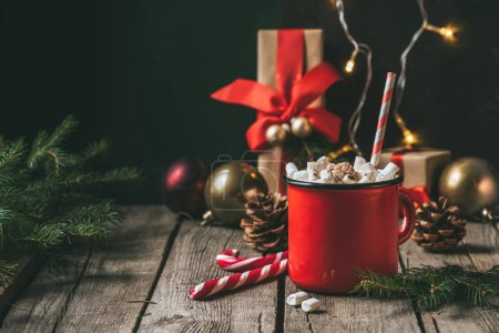 cup of hot cocoa with marshmallows on wooden table with christmas fir tree