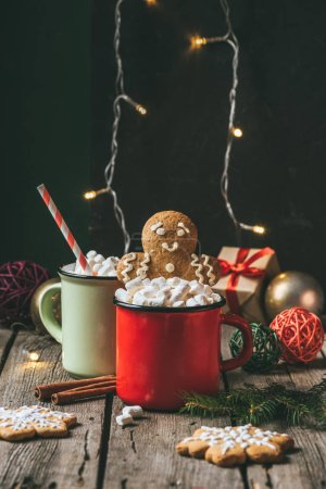 two cups of cocoa with marshmallows and gingerbread man on wooden table with christmas light garland