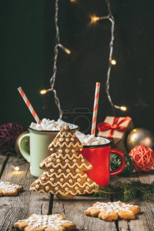 two cups of christmas cocoa with marshmallows and gingerbread christmas tree