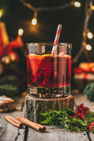glass of mulled wine on wooden stump with cinnamon sticks and christmas light garland