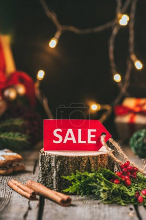 red christmas sale tag on wooden stump with cinnamon sticks and light garland