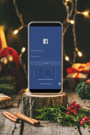smartphone with facebook app on wooden stump with christmas decoration