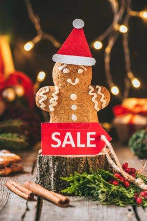 Foto de Hombre de jengibre de Navidad sombrero de santa con venta rojo de la etiqueta en el tocón de madera - Imagen libre de derechos