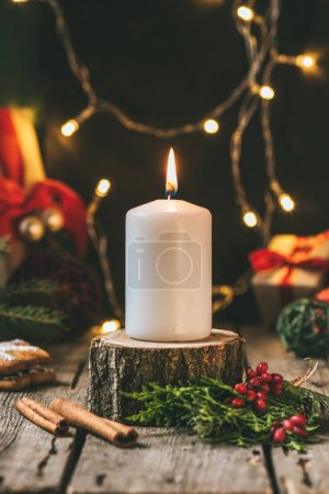 christmas candle on wooden stump with light garland