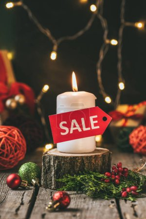 christmas candle with red sale tag on wooden stump