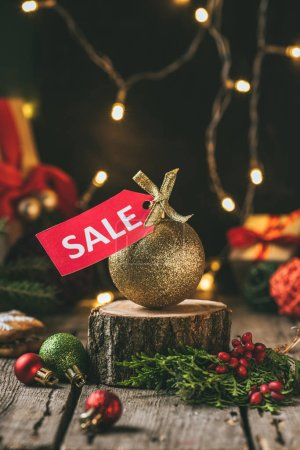 golden christmas ball with red sale tag on wooden stump with light garland
