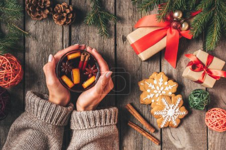 cropped view of woman holding glass with hot mulled wine on wooden background with christmas gifts