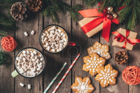 flat lay with gingerbread, christmas gifts and cups of cocoa with marshmallows on wooden background with fir tree