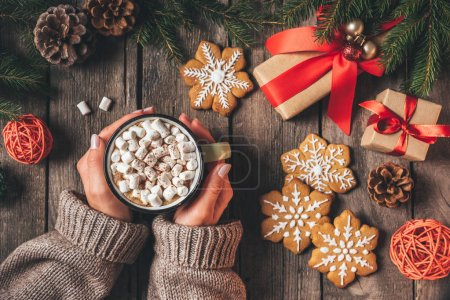 cropped view of woman holding cup of cocoa with marshmallows and gingerbread on wooden background with christmas gifts