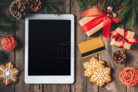 flat lay with digital tablet, credit card, cookies and christmas gifts on wooden background