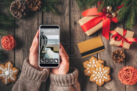 cropped view of woman using smartphone with ticket app on wooden background with credit card and christmas presents