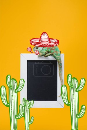 beautiful colorful chameleon in sombrero hat with maracas on blackboard isolated on yellow with mexican cactuses