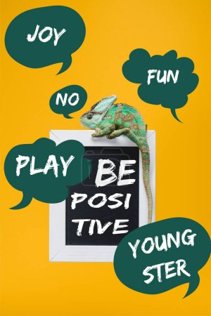 "Photo for Colorful chameleon on blackboard with ""be positive"" lettering isolated on yellow with play, joy, fun, youngster signs - Royalty Free Image"