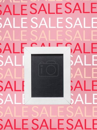empty blackboard in white frame on pink background with sale signs