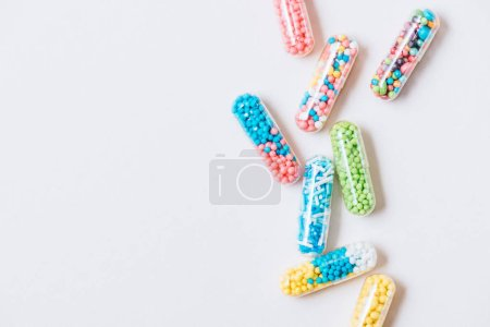 top view of different colorful medical capsules on white surface