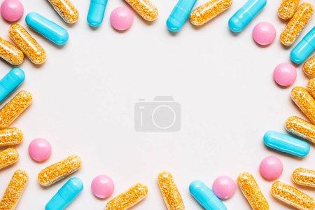 Photo pour Vue de dessus du cadre fait de diverses pilules colorées sur la surface blanche - image libre de droit