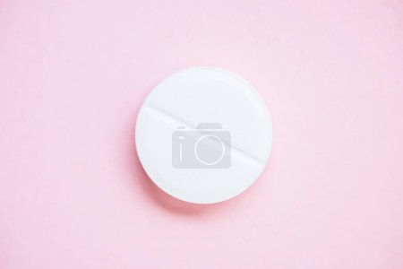 top view of medical pill on pink surface
