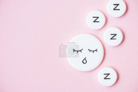 top view of sleeping pills with drawn face and Z signs on pink