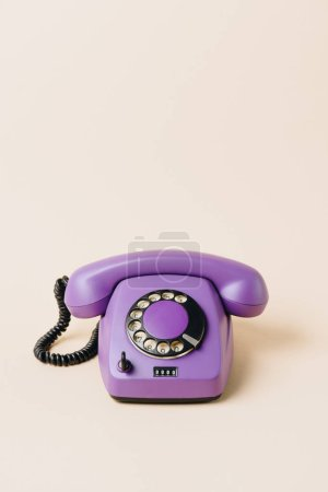 Photo for One purple vintage telephone on beige - Royalty Free Image