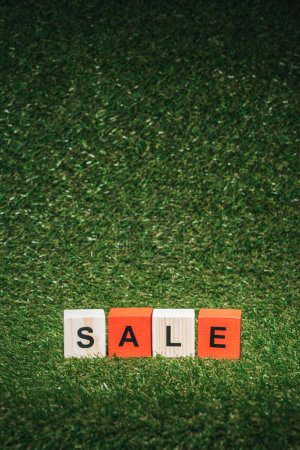red and wooden alphabet cubes with sale sign on green grass