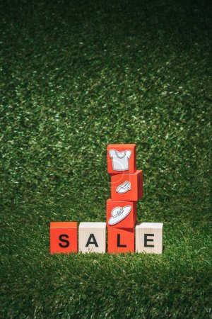 red and wooden alphabet cubes with sale sign and clothes on green grass for black friday