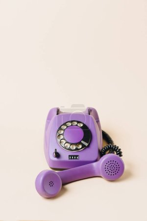 Photo for Purple vintage rotary telephone with tube on beige - Royalty Free Image