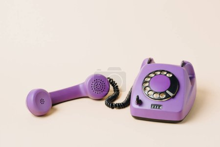 Photo for Purple retro rotary phone with tube on beige - Royalty Free Image