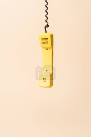 Photo for Yellow vintage phone tube on beige - Royalty Free Image