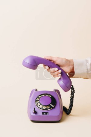 cropped view of woman holding phone tube of purple rotary phone on beige