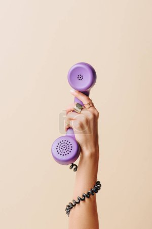 Photo for Partial view of woman holding purple phone tube on beige - Royalty Free Image